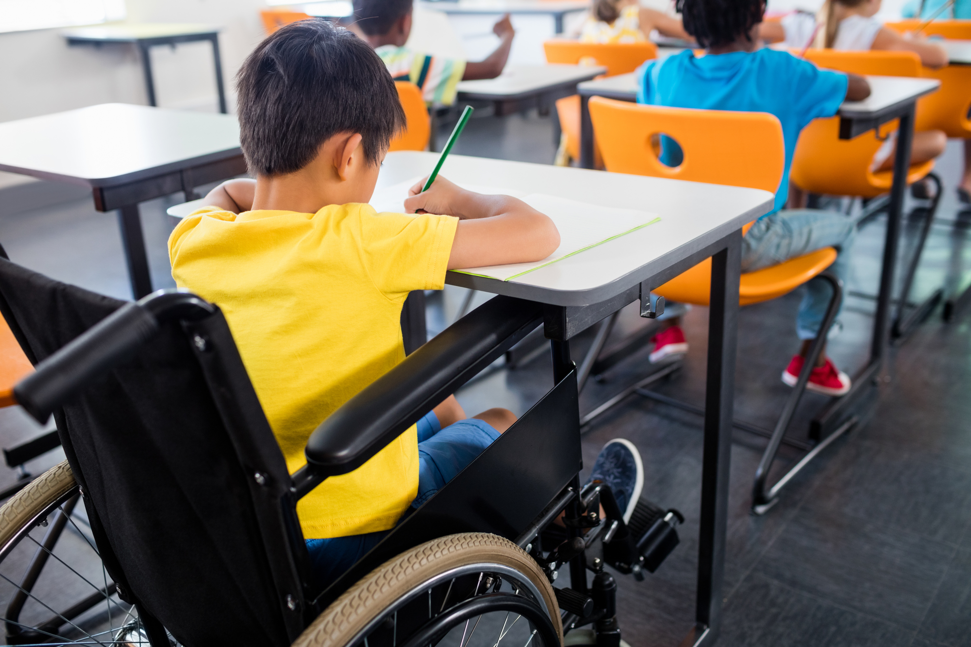 A pupil in wheel chair working at his desk at school